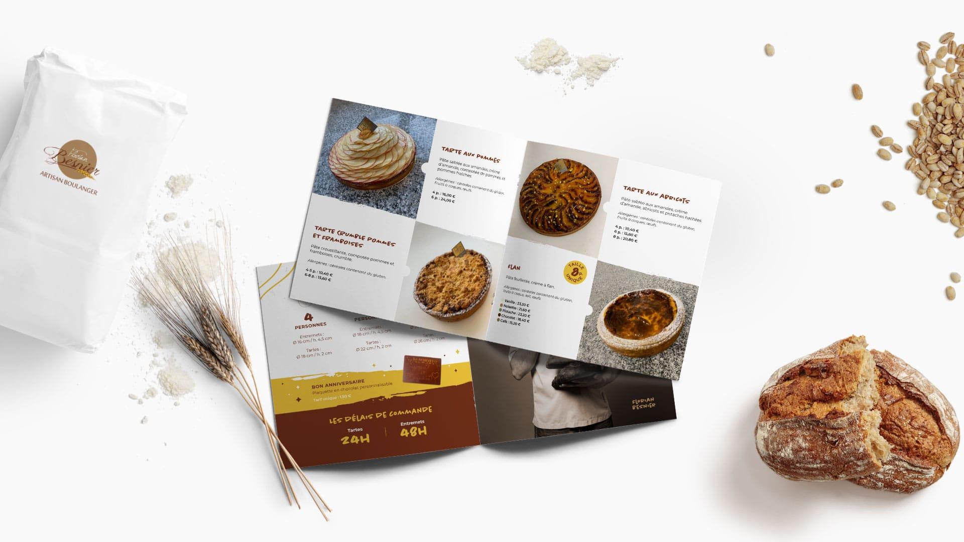 Mise en scène, avec des éléments typiques de la boulangerie, de la carte de printemps 2021 ouverte avec gâteaux et tartes